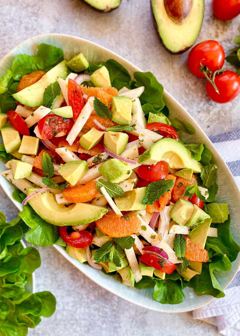 Quick and Easy Lunch Salad over a bed of lettuce. The oval serving bowl is filled with a salad of avocado, tomatoes, oranges, mint, red onion and jicama.