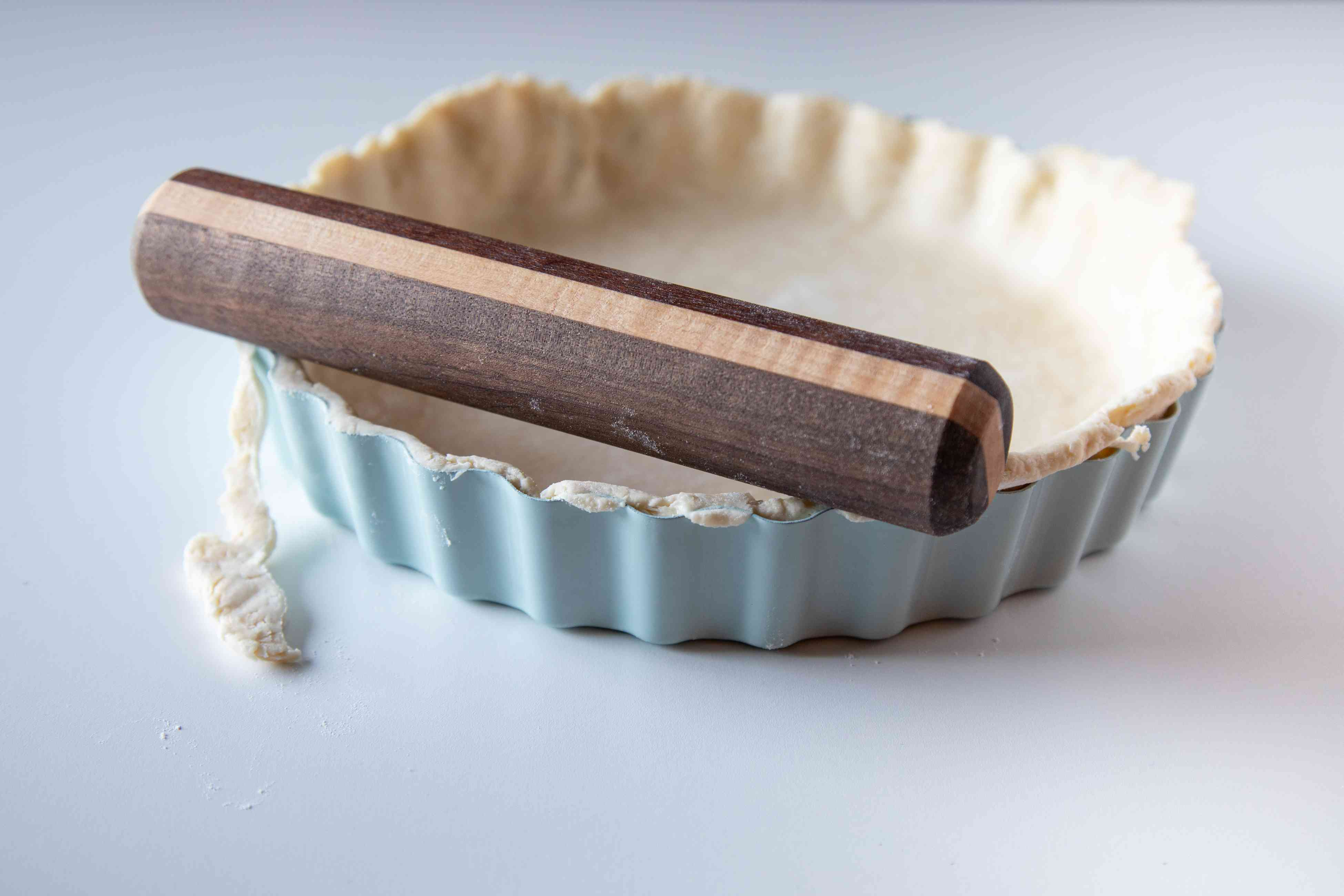 Rolling a rolling pin over the top of a tart crust to make a quiche lorraine recipe.