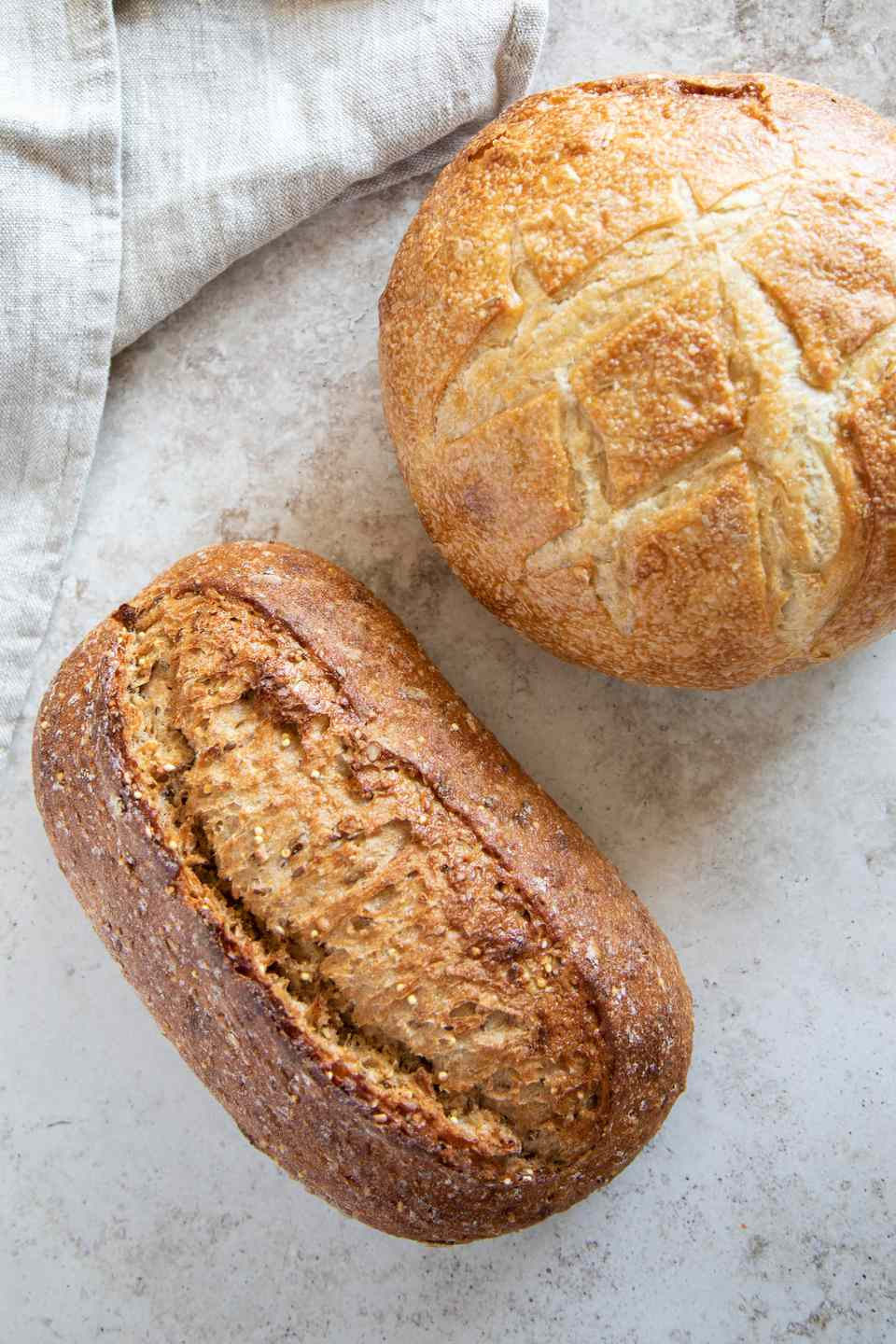Two artisan loaves of bread on marbled surface