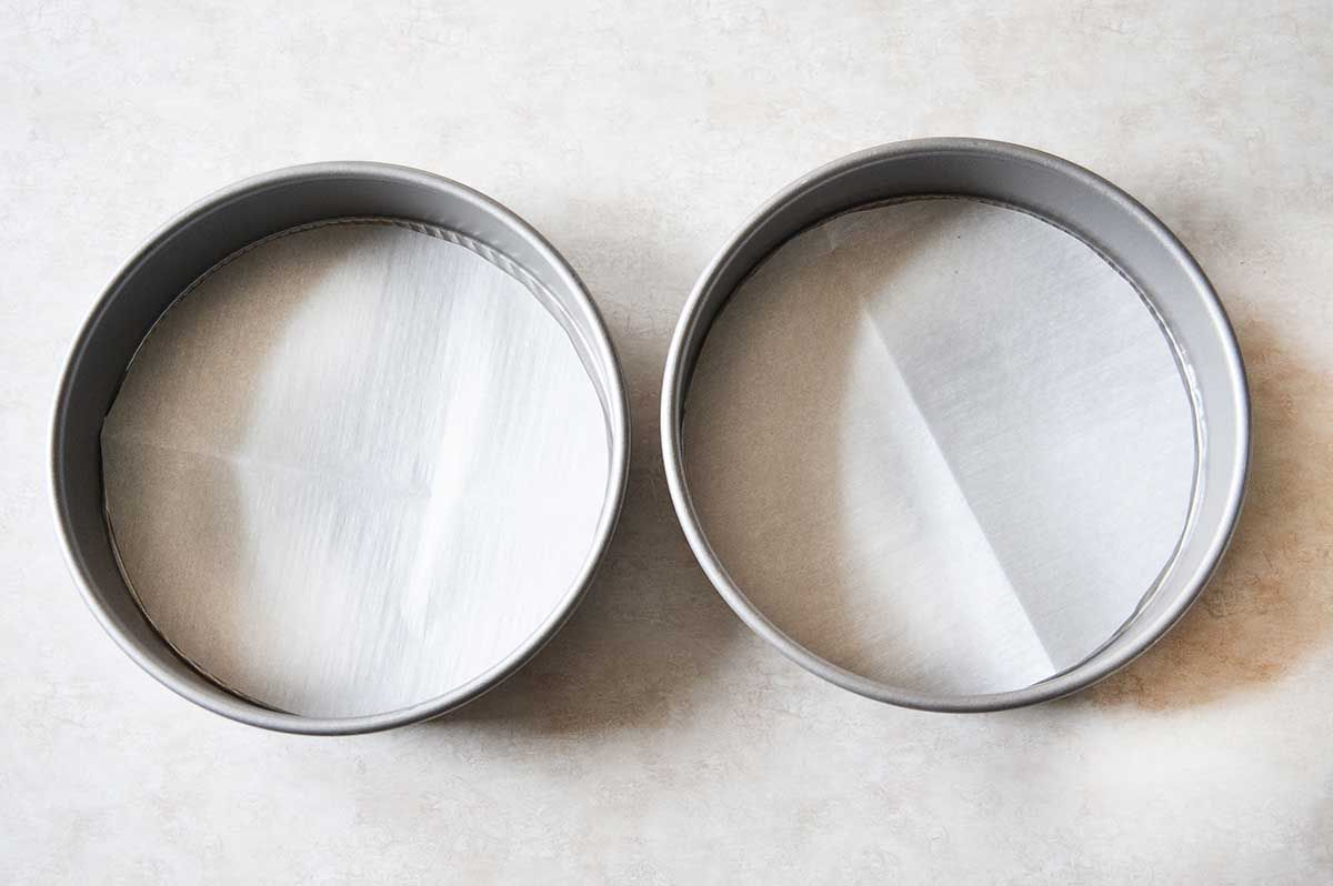 Two round cake pans lined with parchment.