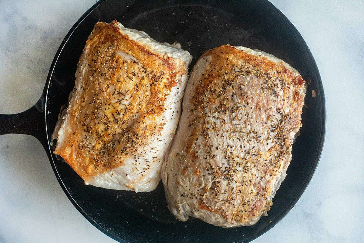 Two pork loins next to each other in a cast iron skillet to make a Glazed Slow Cooker Pork Loin.