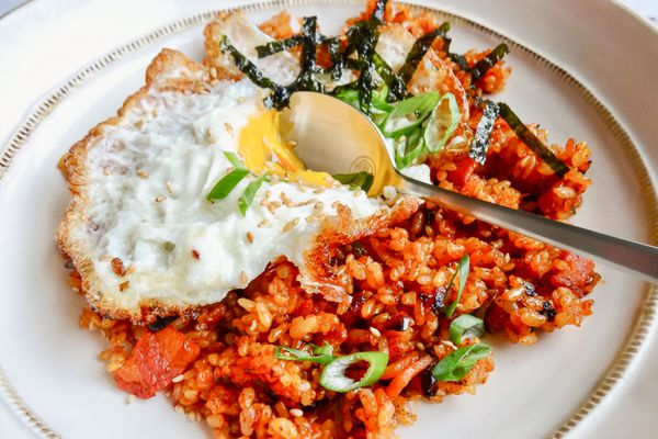 Kimchi fried rice with a fried egg served on a white plate.