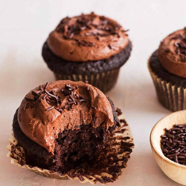 Cupcakes with chocolate frosting with a bite taken out and on a counter.