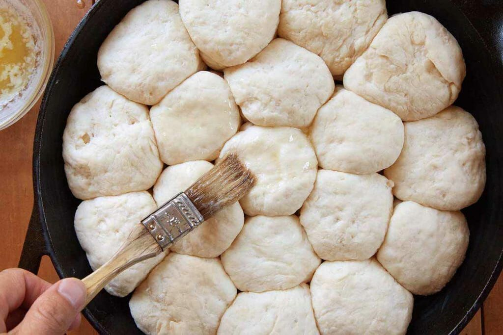 Brush angel biscuit dough with butter before baking in a cast iron skillet