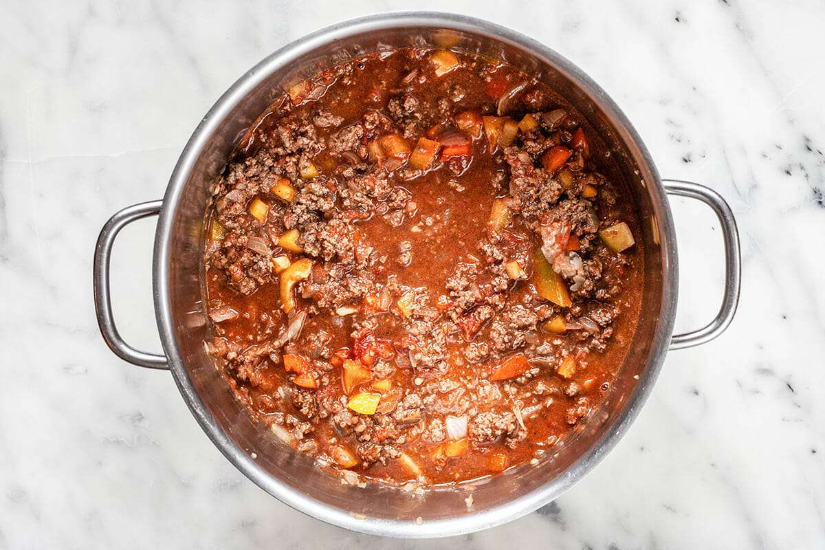 Ground beef chili simmering in a large stock pot.