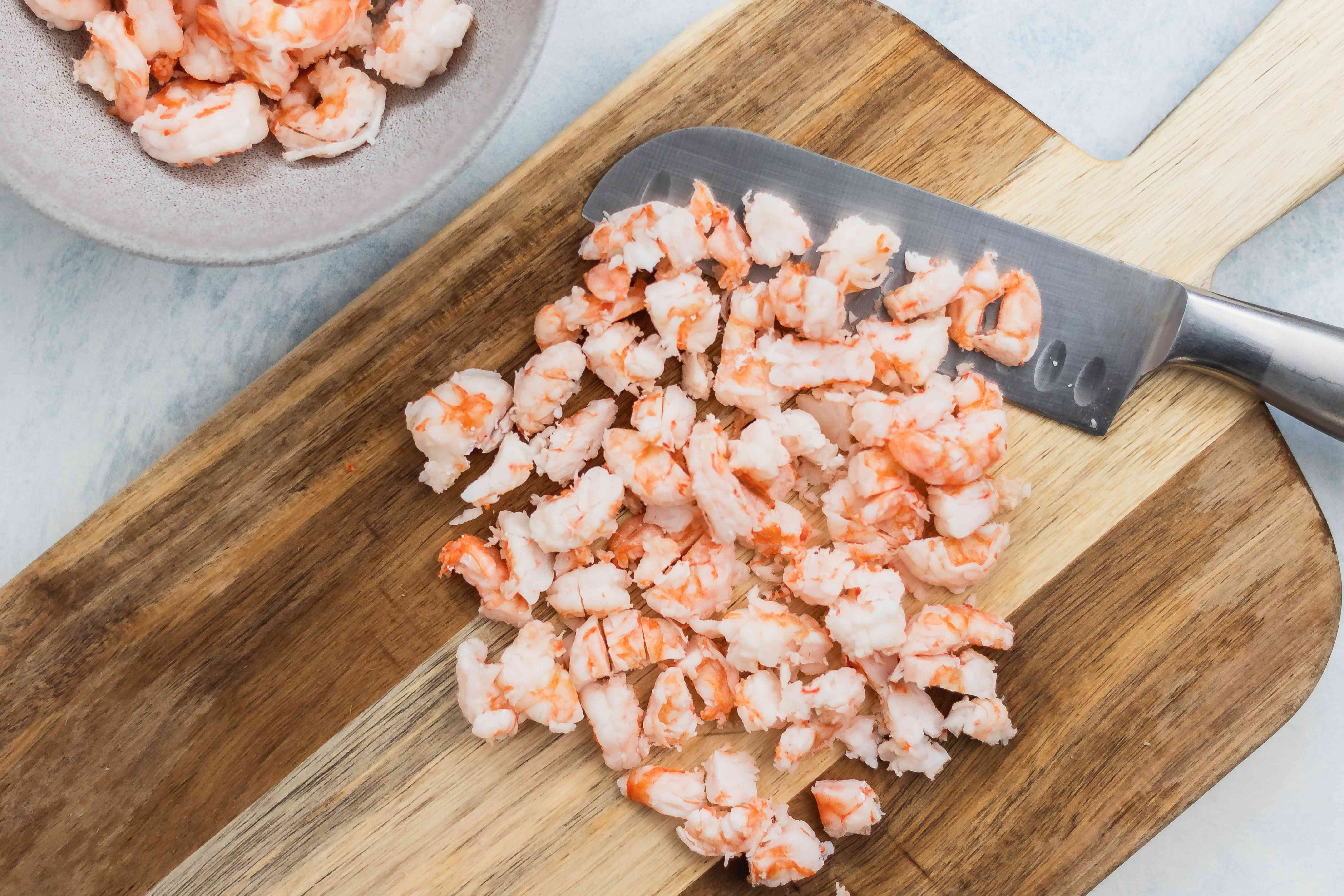 Chopping shrimp to show how to make shrimp cocktail.