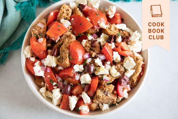 Overhead view of a white bowl filled with Cretan Dakos salad.