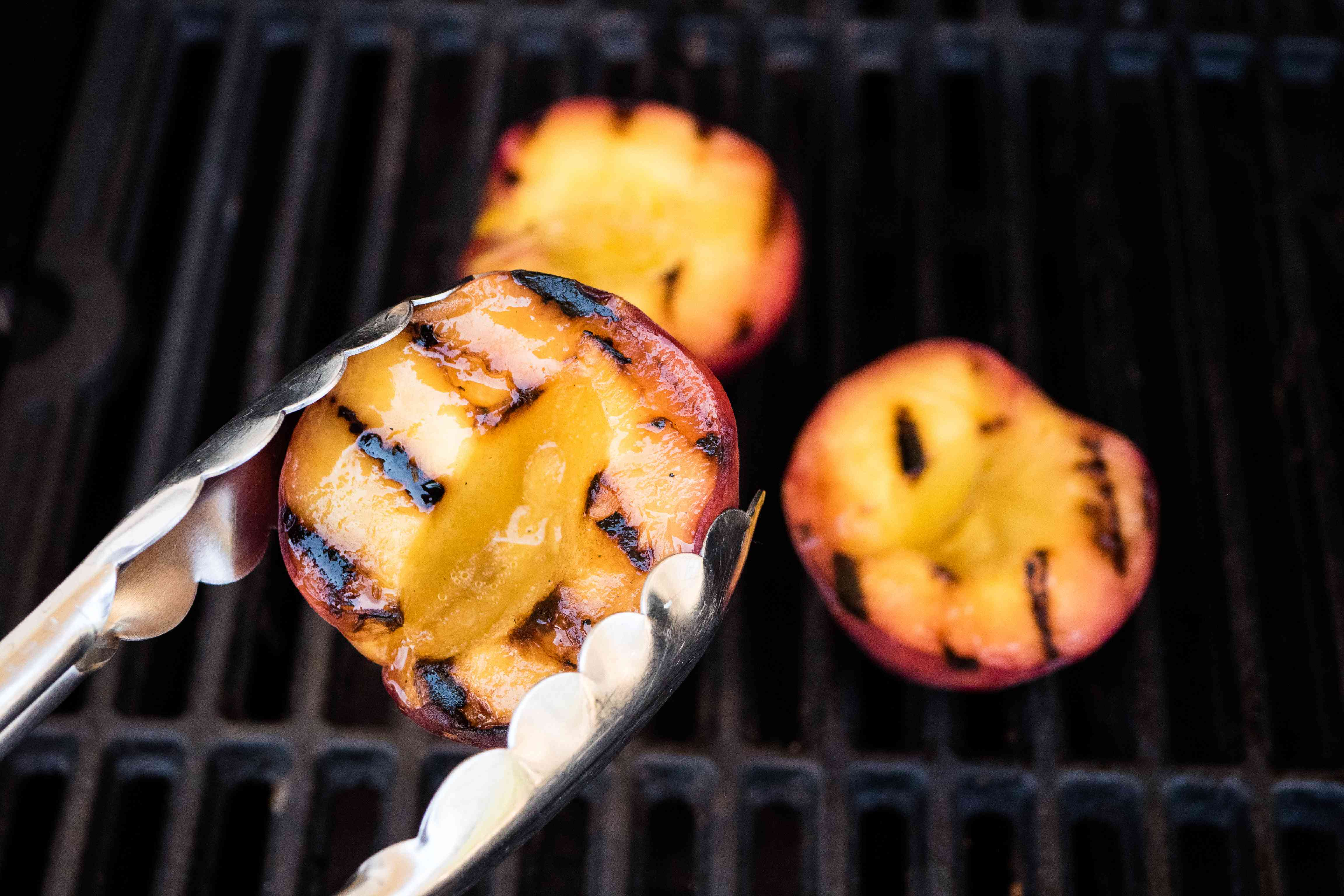 Holding a grilled peach with tongs to make a grilled peach margarita.