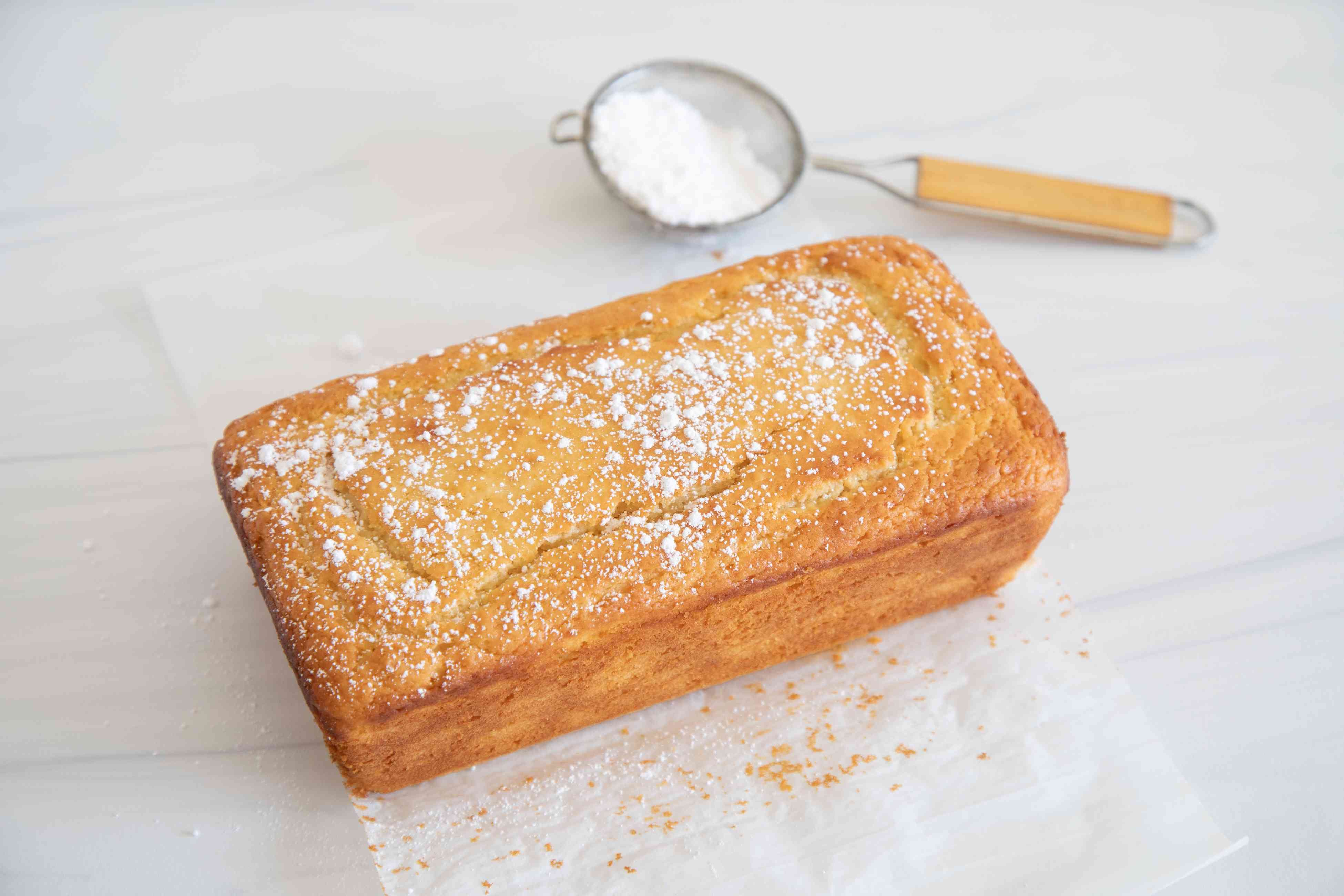 A loaf of Quick and Easy Yogurt Cake dusted with powdered sugar.