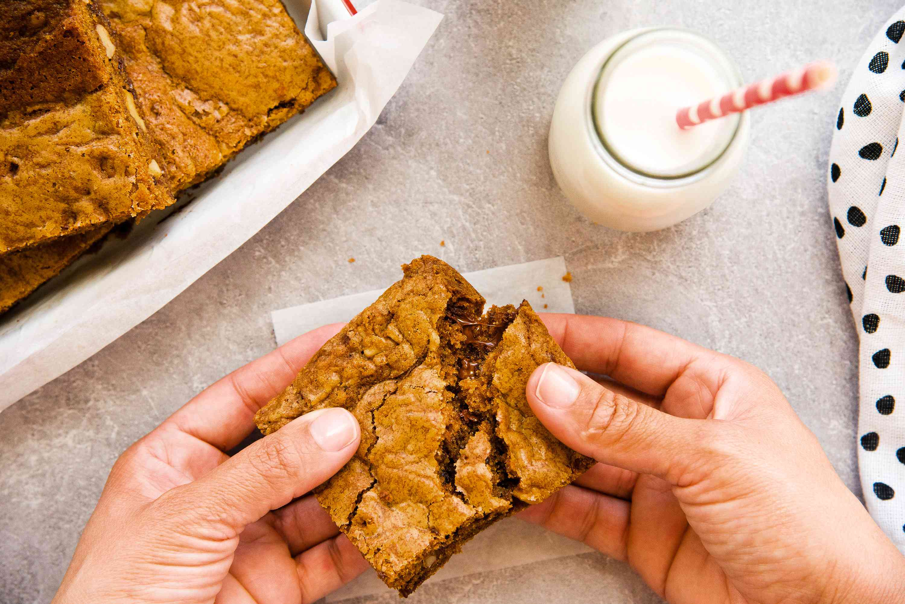 Breaking a chocolate chip cookie bar using two hands.