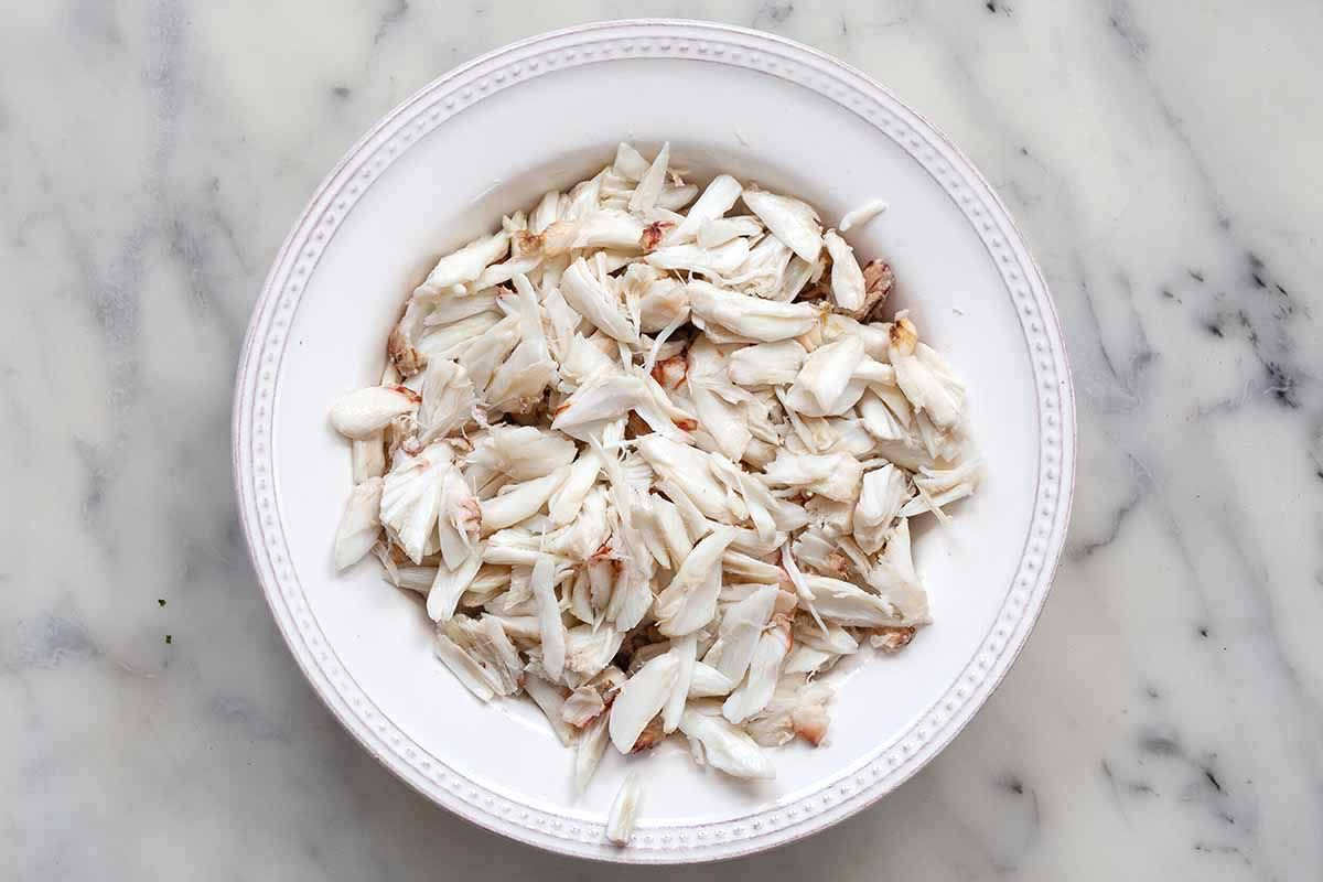 Lump crab meat broken up into smaller pieces on a white plate.