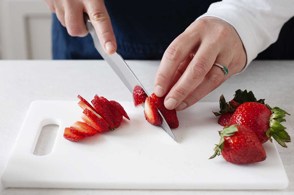 Strawberries being sliced on a white cutting board.