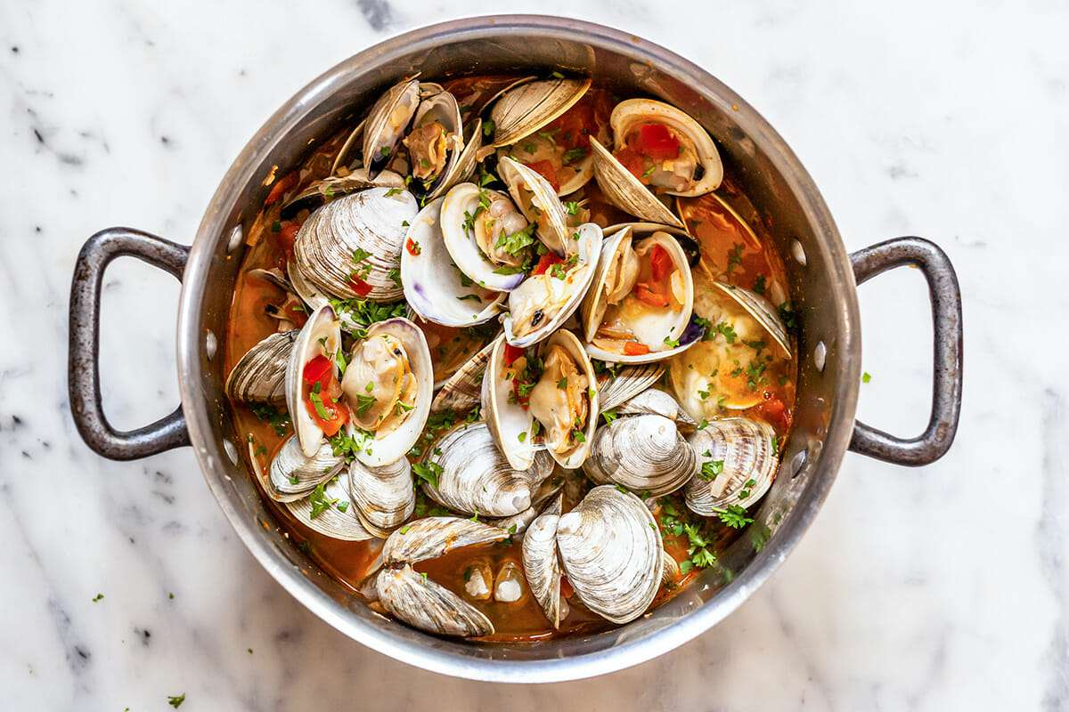Steamed clams with chorizo in a large stock pot. The brothy clams are open and chopped tomatoes are sprinkled over the top.