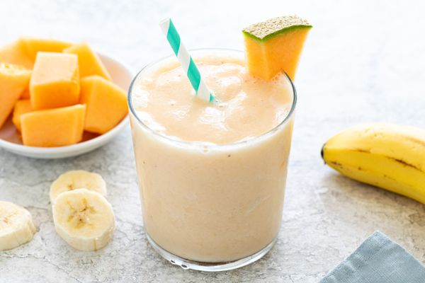 Simple cantaloupe smoothie in a glass and garnished with a slice cantaloupe.
