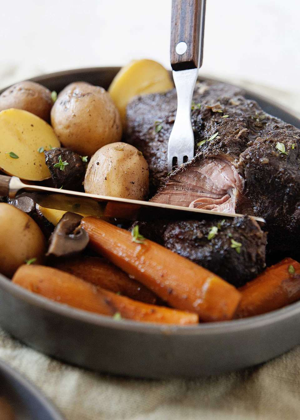 Close up of tender crock pot roast made in a slow cooker with gracy, cooked carrots and potatoes with a fork and knife.