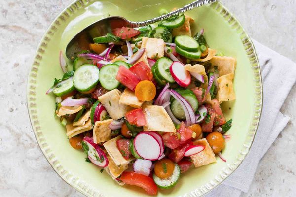 Fattoush with summer vegetables and pita chips in a round bowl