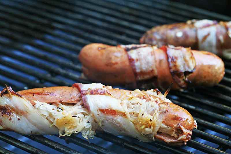 how to grill hot dogs stuffed with sauerkraut and wrapped in bacon