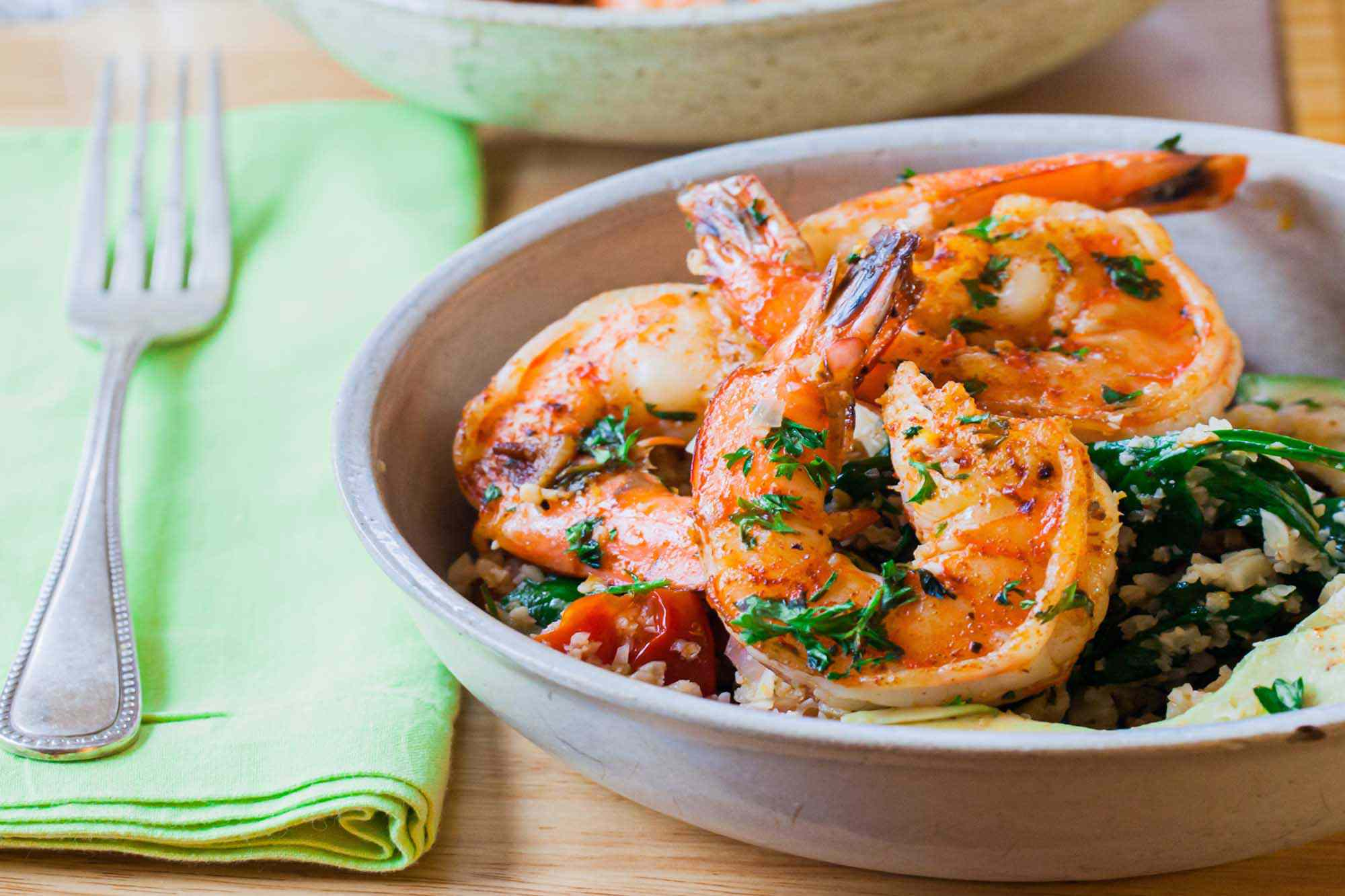 A shallow bowl of garlic shrimp cauliflower rice with a napkin and fork to the left. Sauteed shrimp and herbs are visible in the bowl.