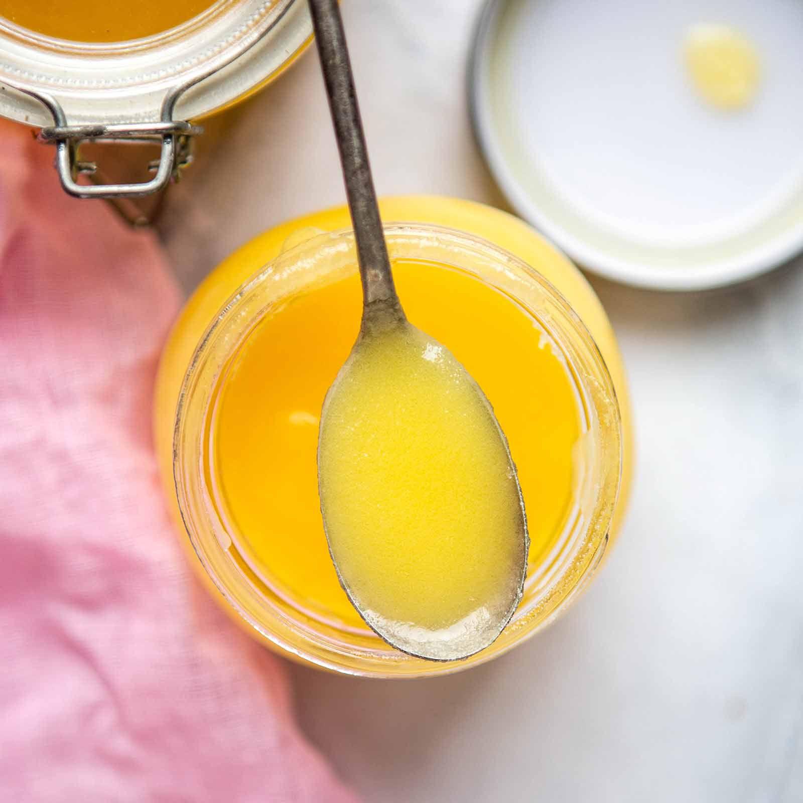 Ghee butter - ghee on spoon over jar
