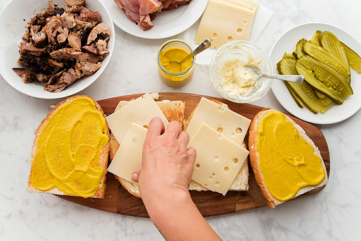 A hand is placing sliced cheese on one quarter of a traditional cuban sandwich. One quarter has two slices of swiss cheese and two quarters are spread with yellow mustard. The sandwich is set on a wooden cutting board set on a marble table top. Bowls and plates of shredded pork, sliced ham, yellow mustard, sliced cheese, mayonnaise and sliced pickles are set above.