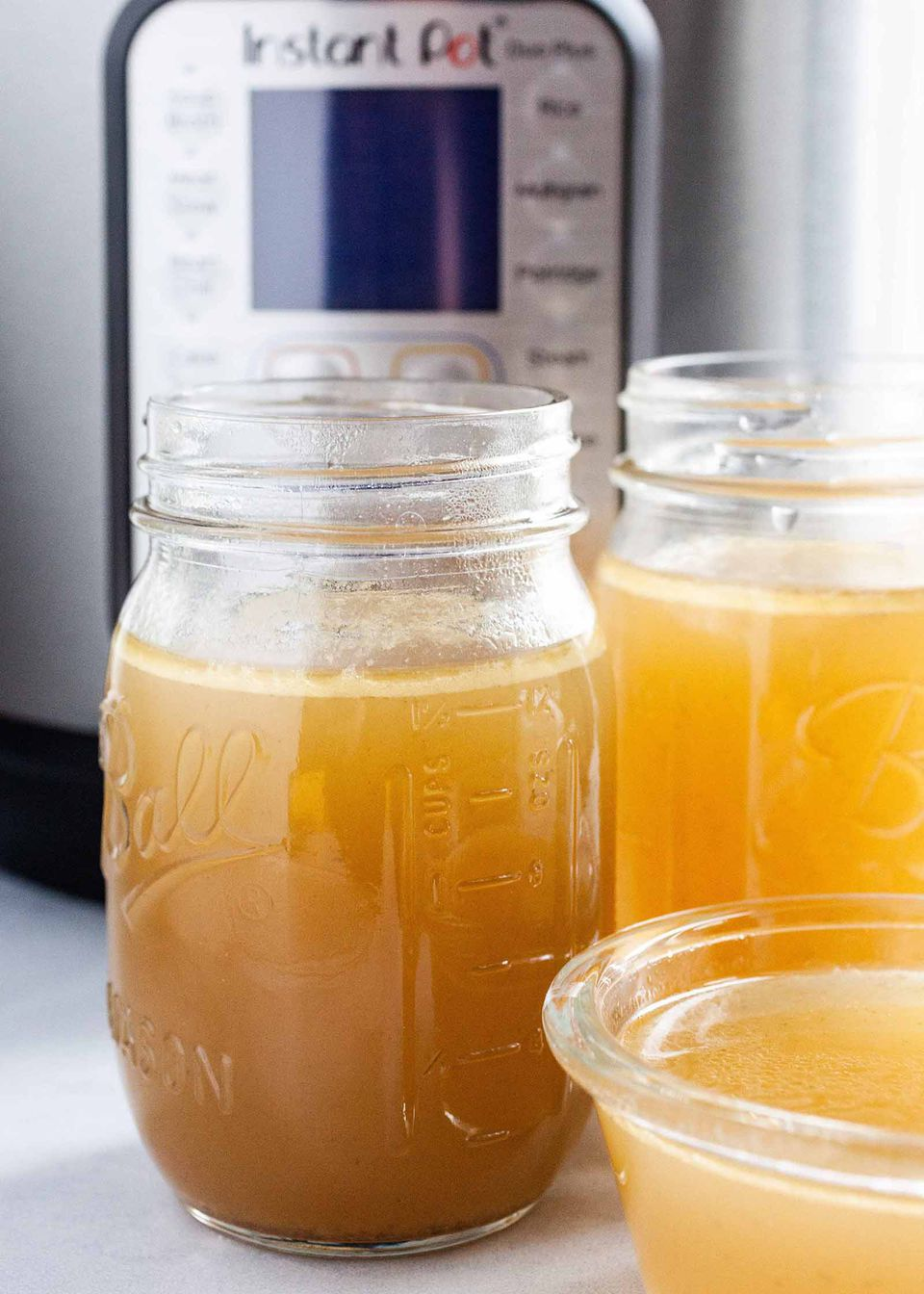 Pressure Cooker Chicken Stock - - two ball jars filled with chicken sock with an instant pot pressure cooker behind them