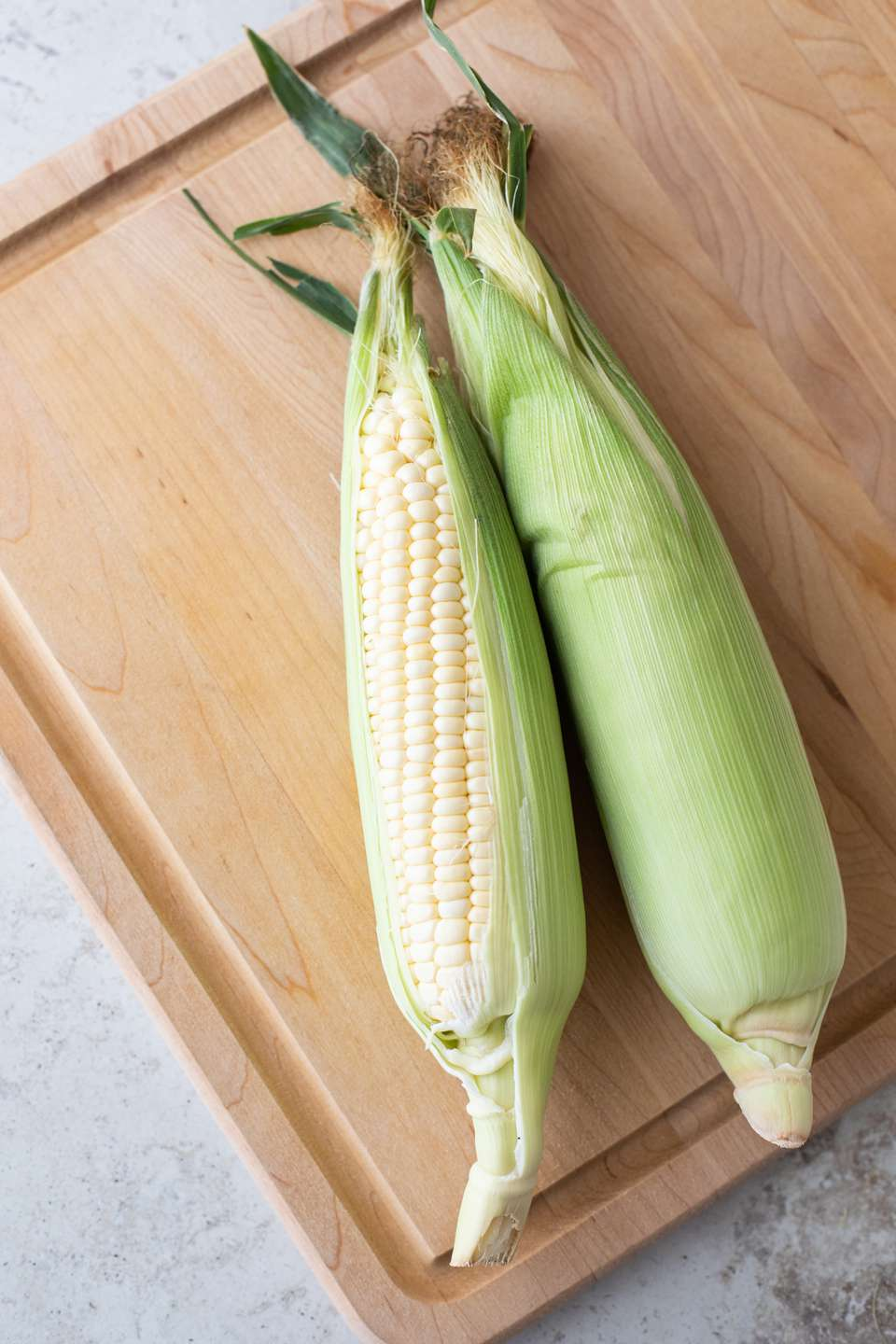 Two ears of corn on a wooden cutting board