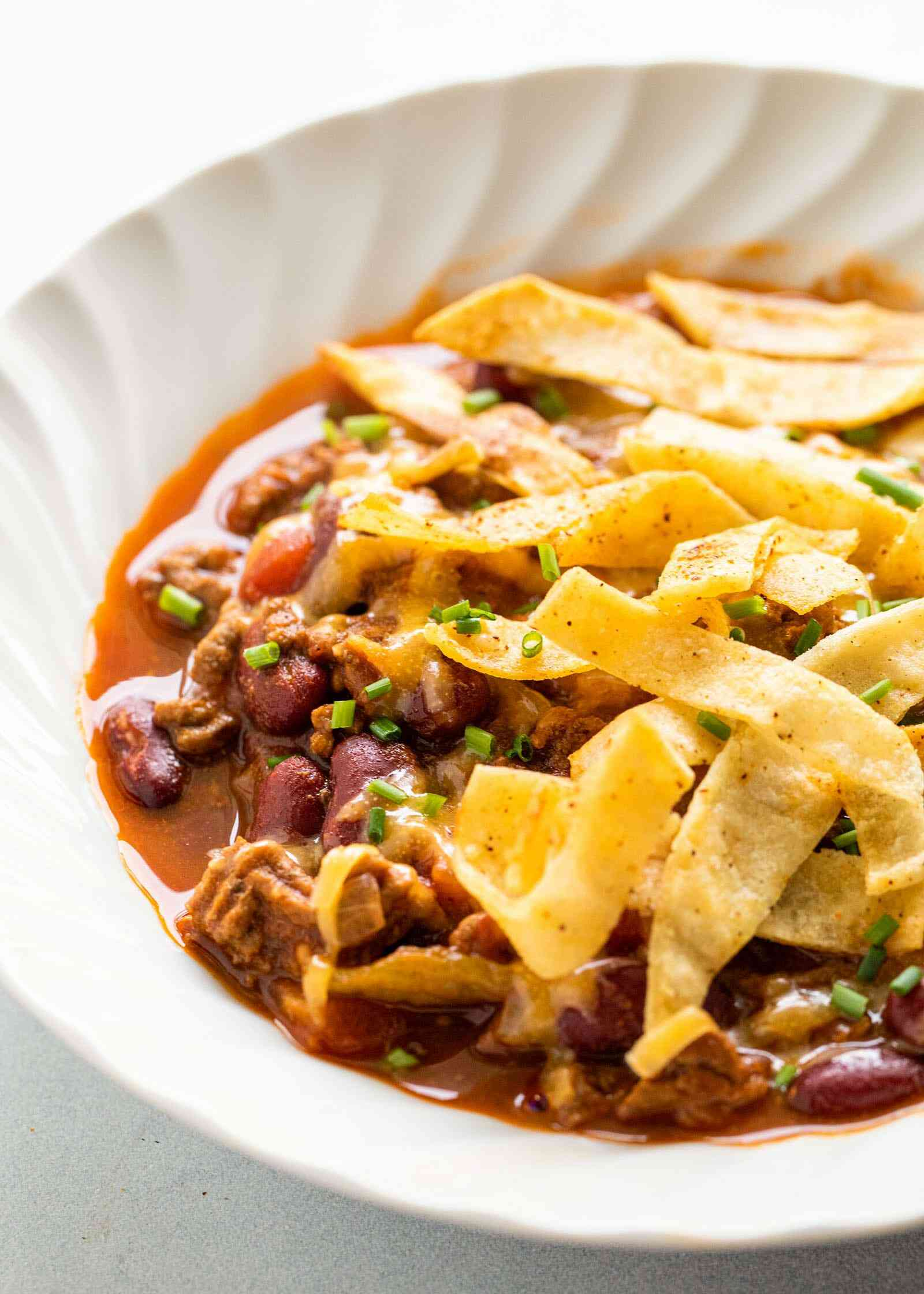 The Best Slow Cooker Chili topped with fried tortilla strips in a white bowl.