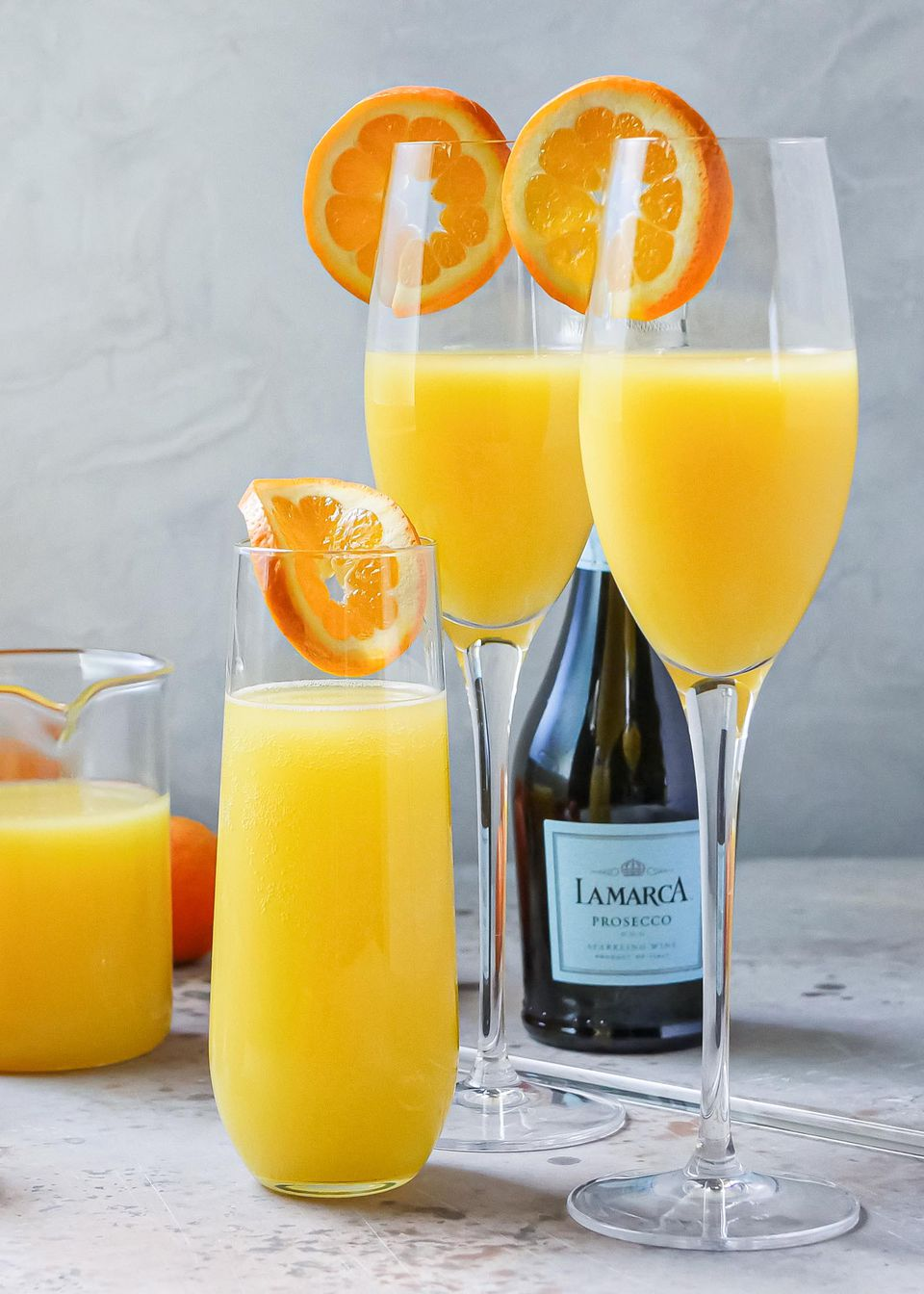 Classic mimosas in champagne flutes. Orange juice and prosecca are behind the glasses.