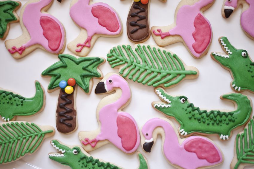 Close-up of homemade decorated biscuits in the shapes of flamingos, palm trees, crocodiles and leaves for a child's birthday party with a tropical jungle theme