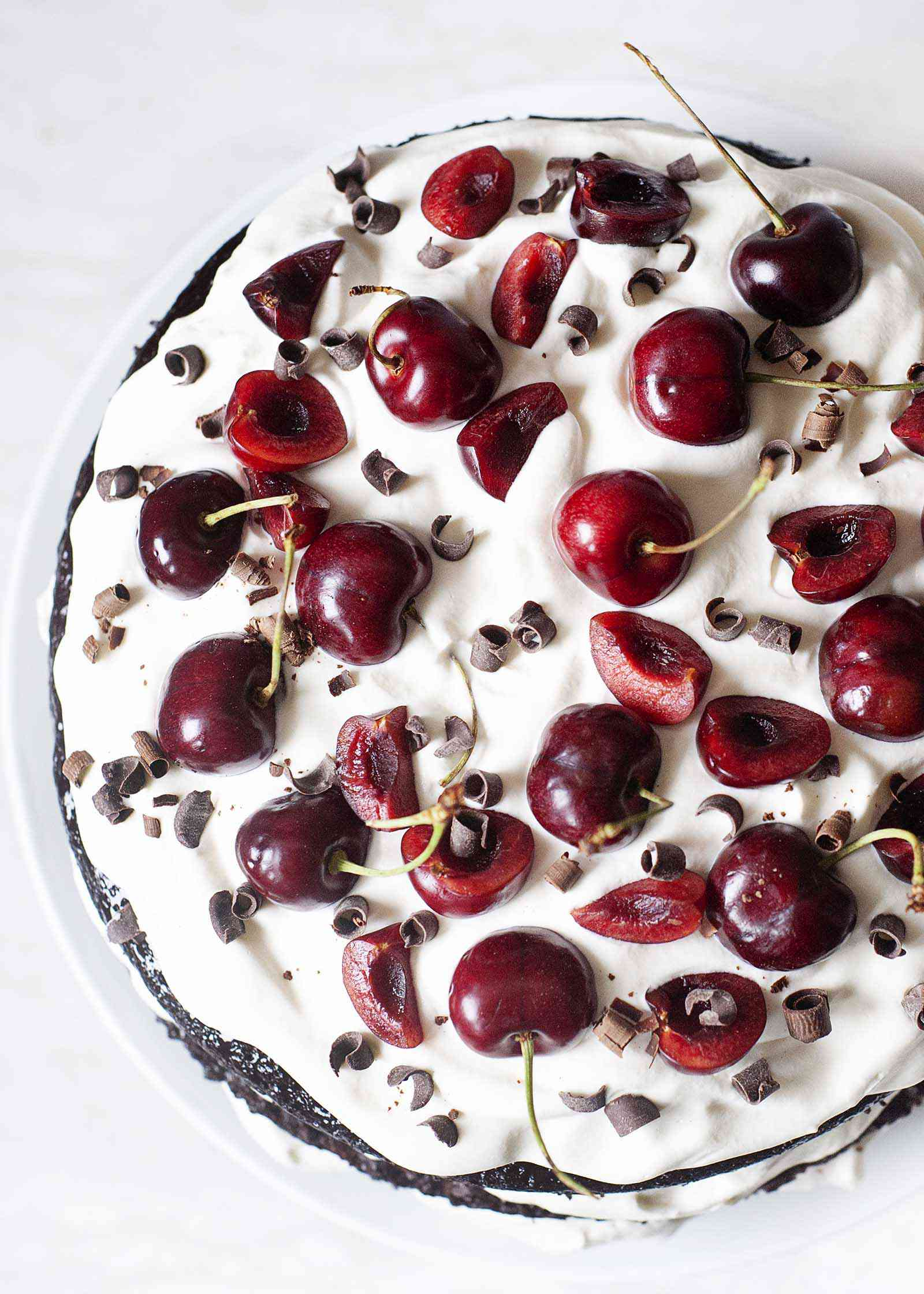 The top of a Cherry Chocolate Cake with Whipped Cream topped with fresh cherries and chocolate.