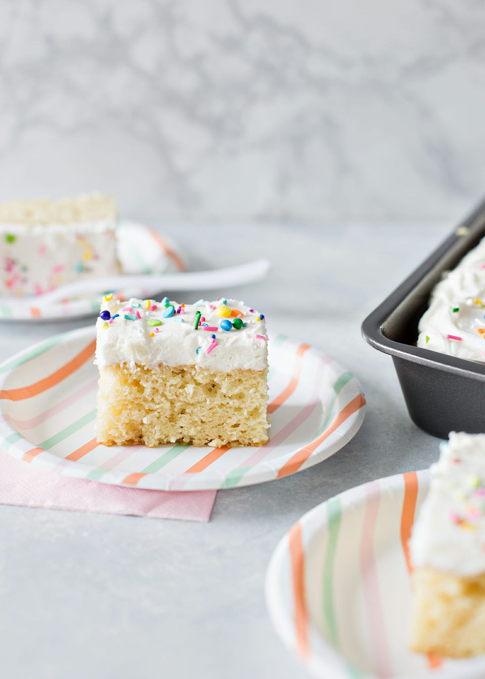 Best Vanilla Cake Recipe - vanilla cake with white frosting and sprinkles on plate.
