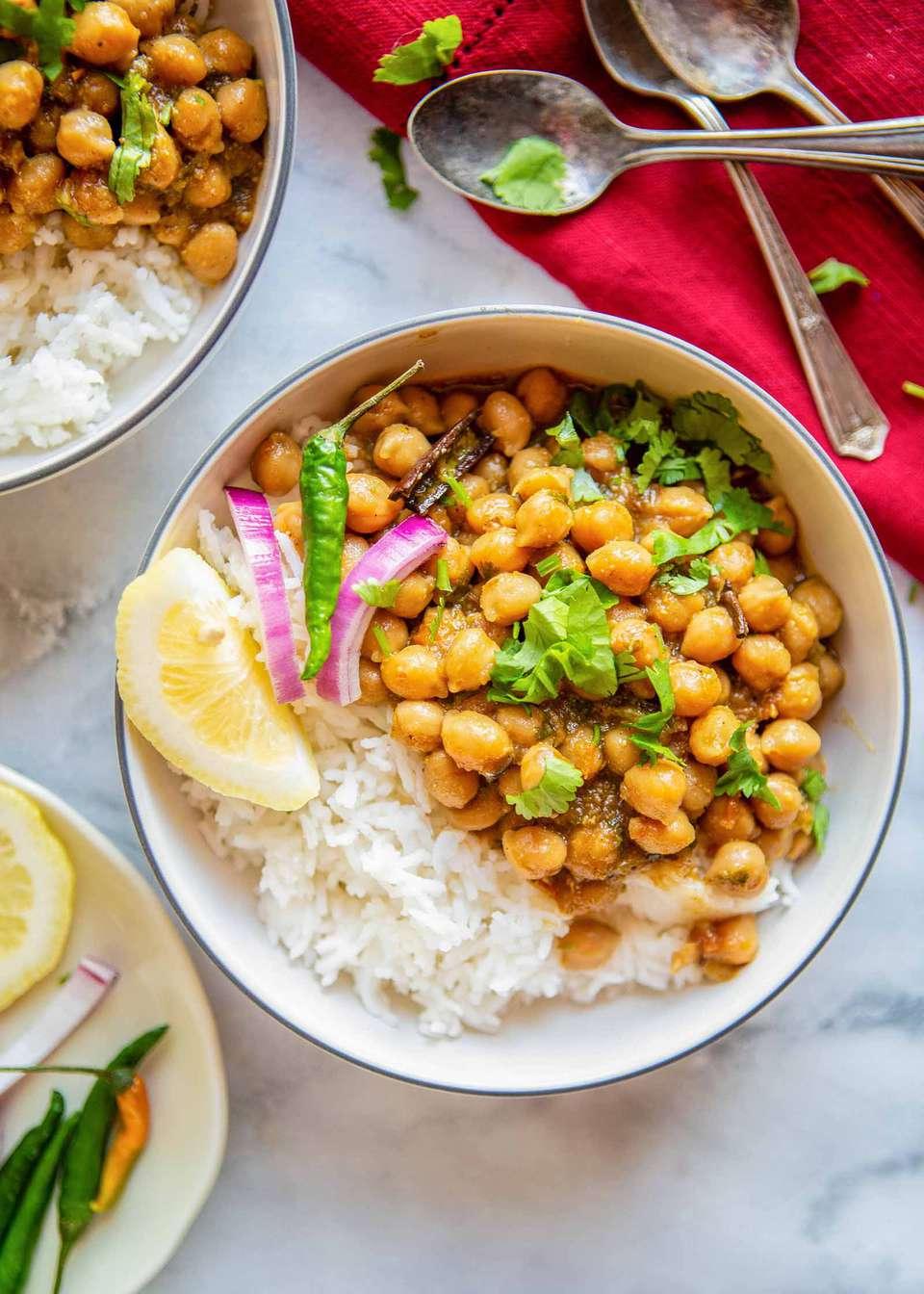 Vegetarian Chana Masala - bowl of chana masala with rice, and lemon wedge