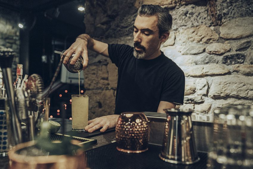 Bartender pouring cocktail in a glass
