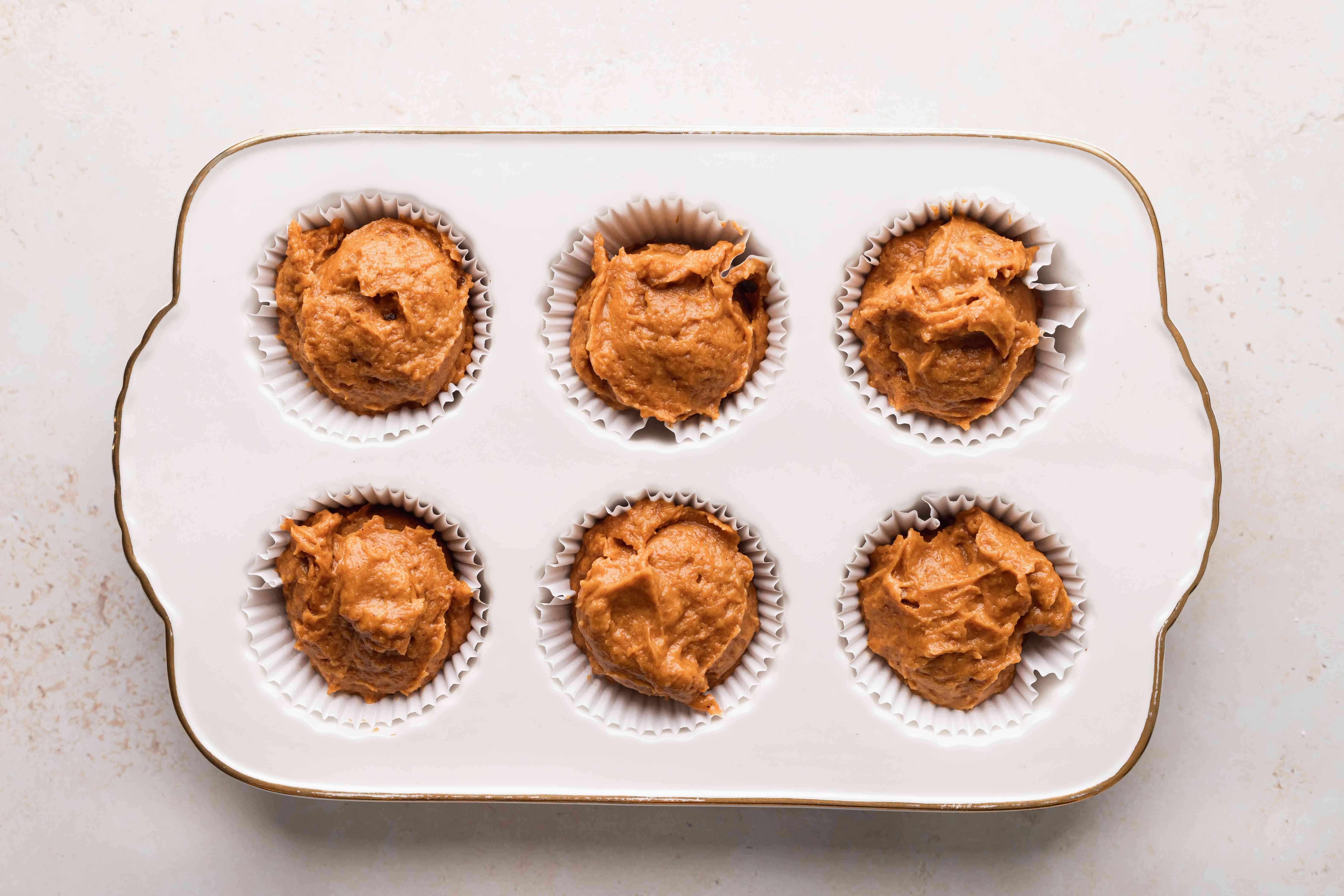 Pumpkin muffin batter in muffin tin.