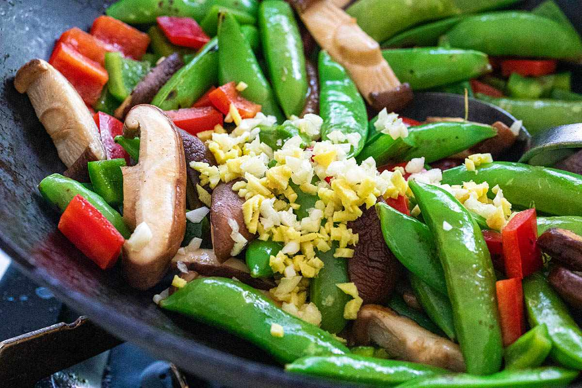 Snap peas, mushrooms, and red peppers in a wok to make an Easy Tofu Stir Fry.