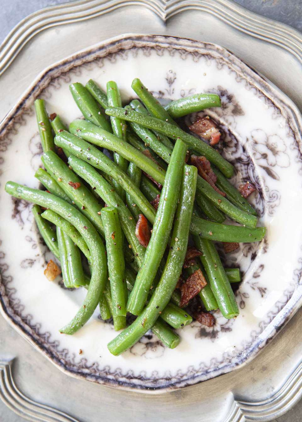Fresh green beans cooked with bacon and served on a plate