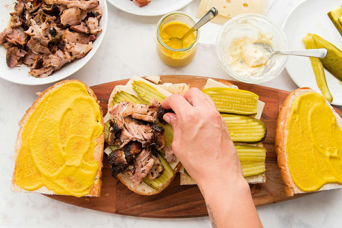Best cuban sandwich is being assembled on a wooden cutting board set on a marble countertop. Hand is placing shredded pork, along with picles and cheese on french bread. Two tops of the bread are covered with yellow mustard and bowls of pork, mustard, mayonnaise and pickles are visible.