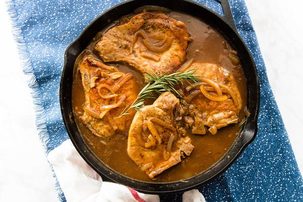 Four gluten free Smothered Pork Chops with Gravy in a skillet with a sprig of rosemary on top set against a blue background.