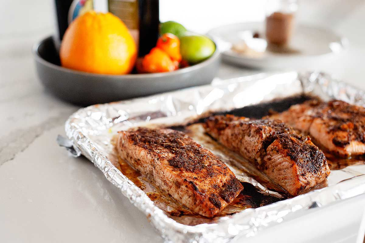 Three fillets of spicy jerk salmon on a foil lined baking tray. A bowl of produce is on the marble counter behind the baking tray.