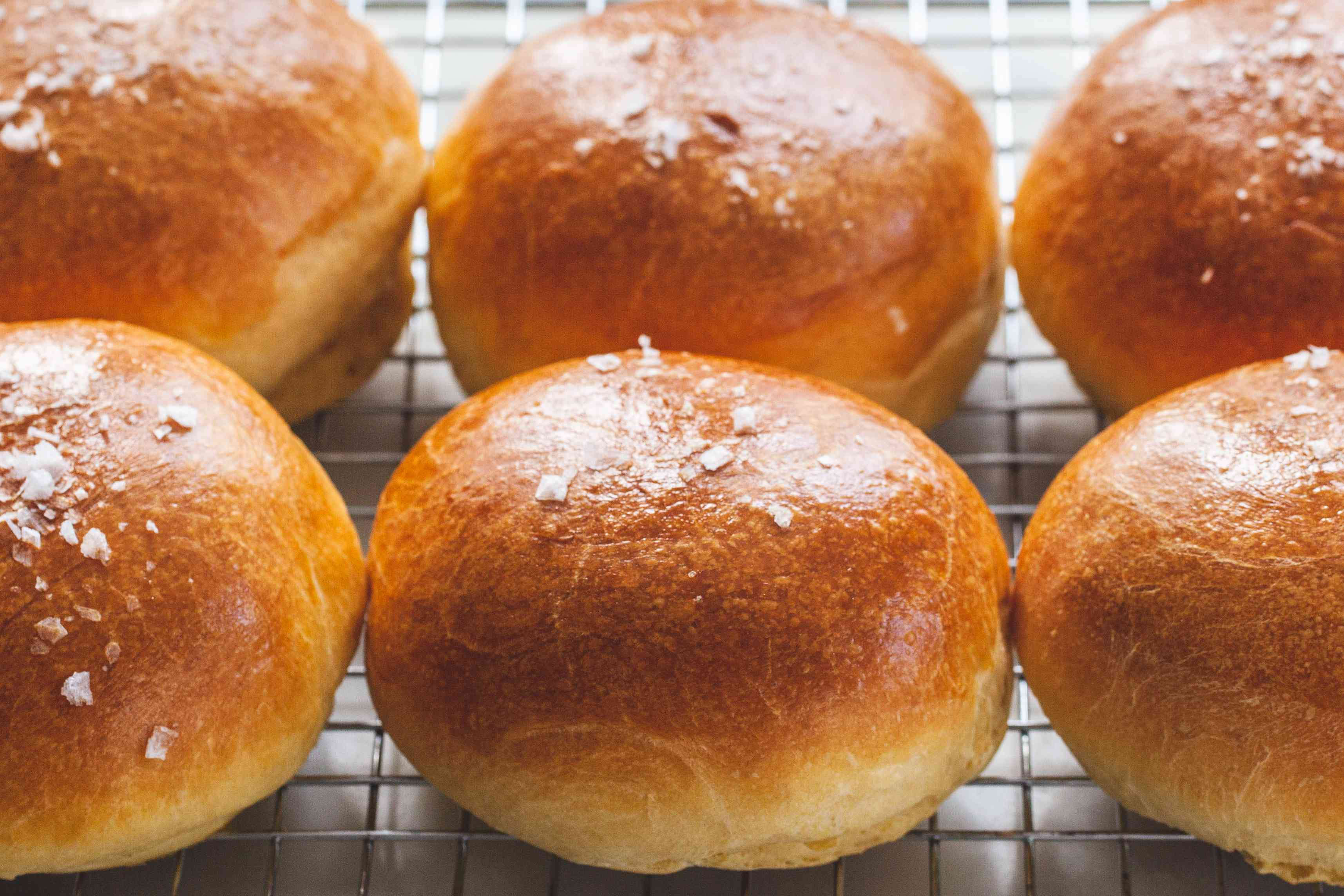 The Fluffiest Brioche Buns cooling on a wire rack.