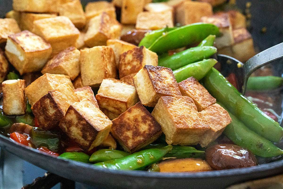 A spoon mixing tofu and vegetables for a Vegetarian Stir Fry with Tofu.