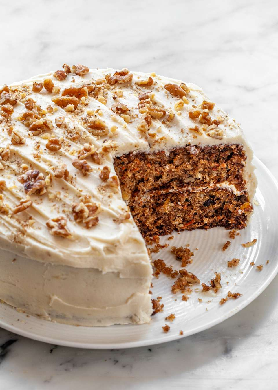 The best carrot cake recipe with a slice removed from the layered cake.