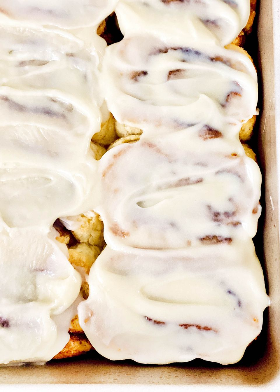 The best gluten free cinnamon rolls topped with frosting and in a pan.