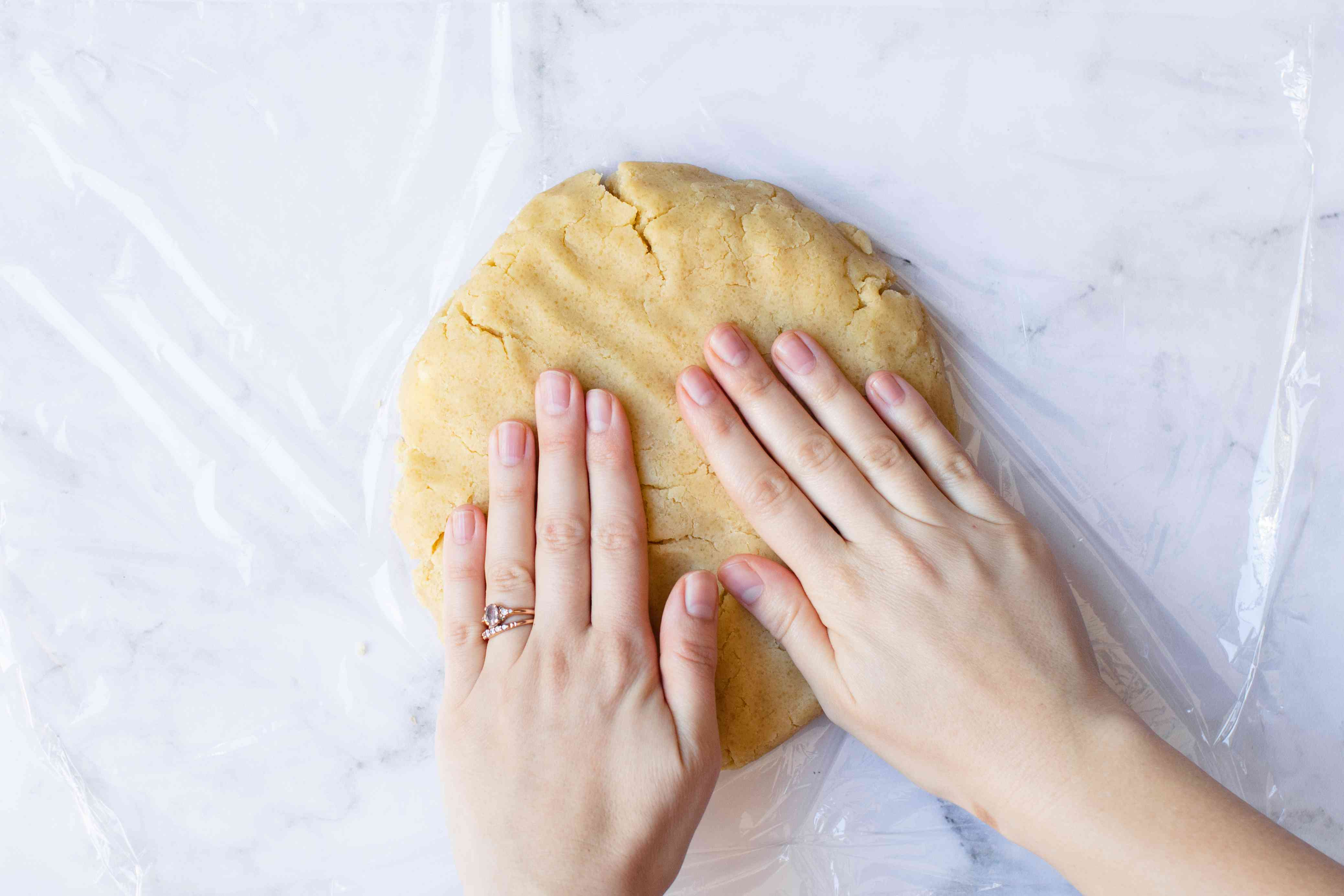 Wrapping almond cookie dough in plastic wrap.