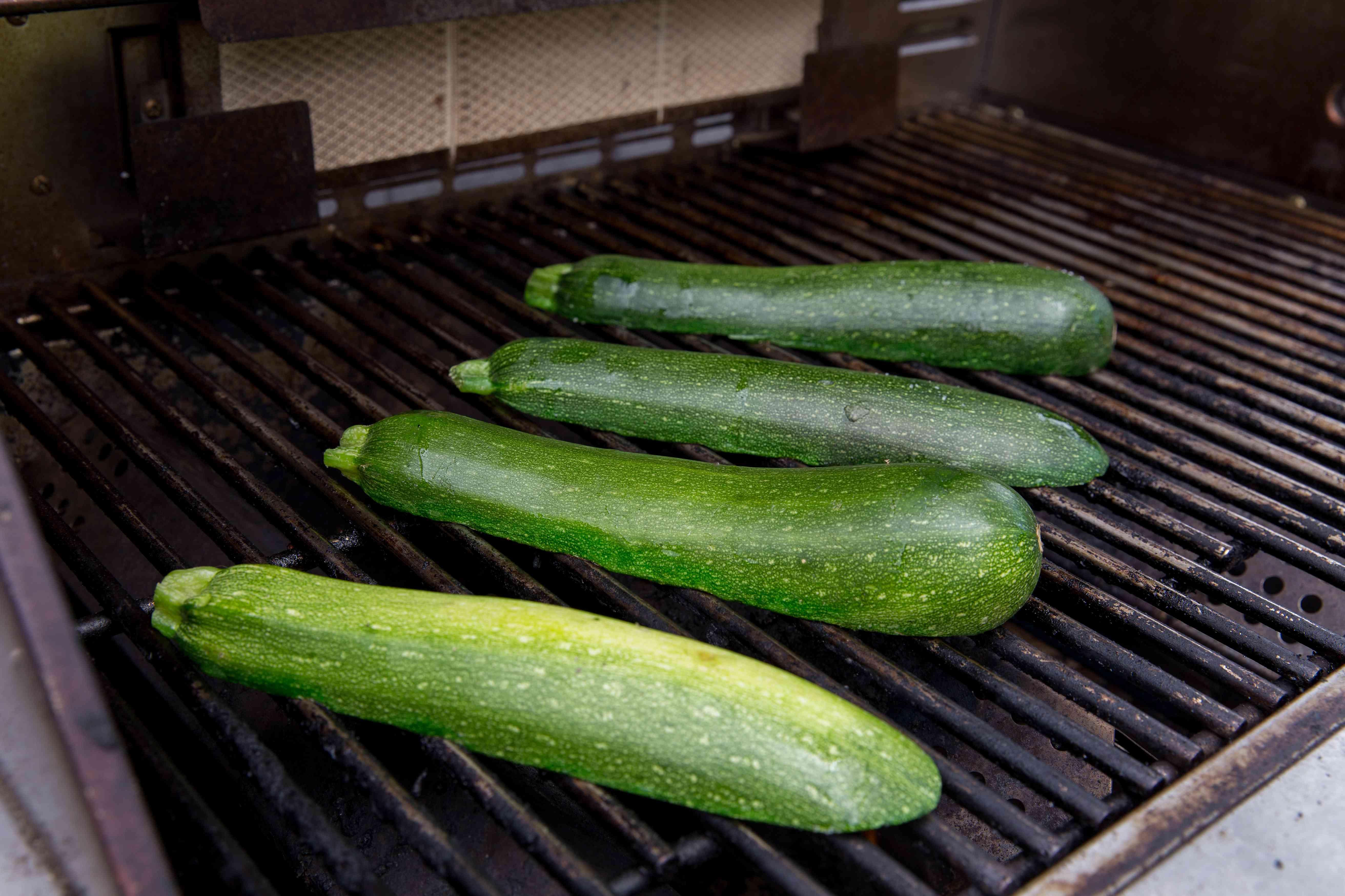 Grilling zucchini boats cut side down to make a grilled zucchini recipe.