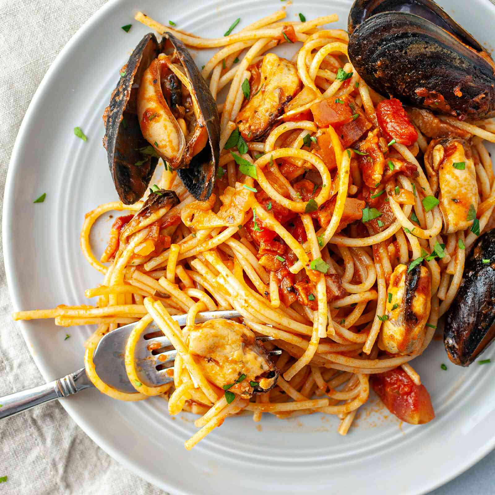 Mussels in Spicy tomato sauce recipe - overhead shot of spaghetti on plate with mussels on side