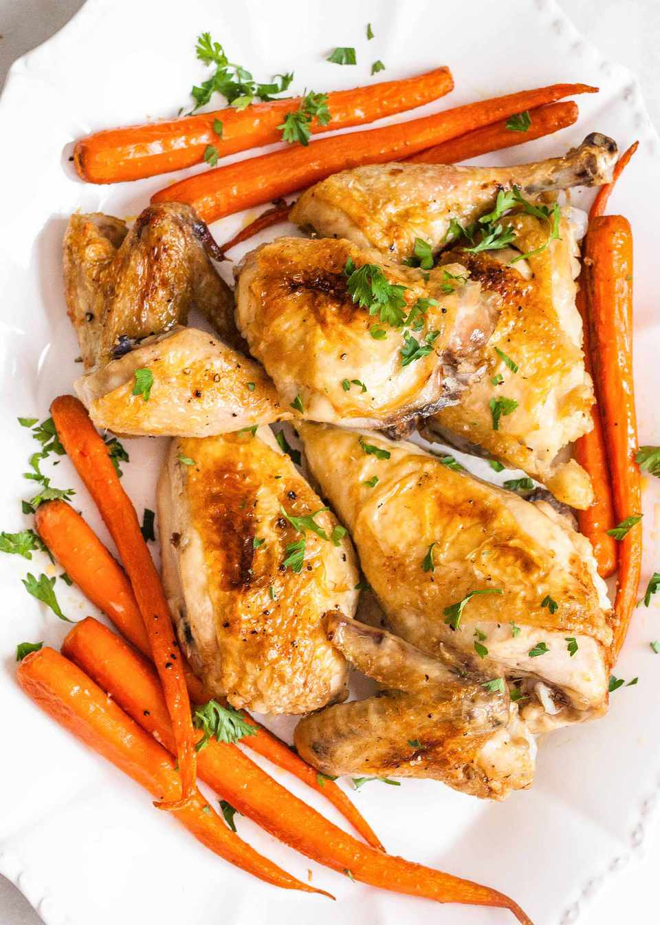 How to Make Chicken in the Oven Chicken cooked with carrots and herbs on white plate