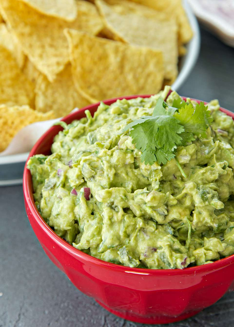 Spicy Guacamole Recipe - guacamole in a bowl wtih chips on the side
