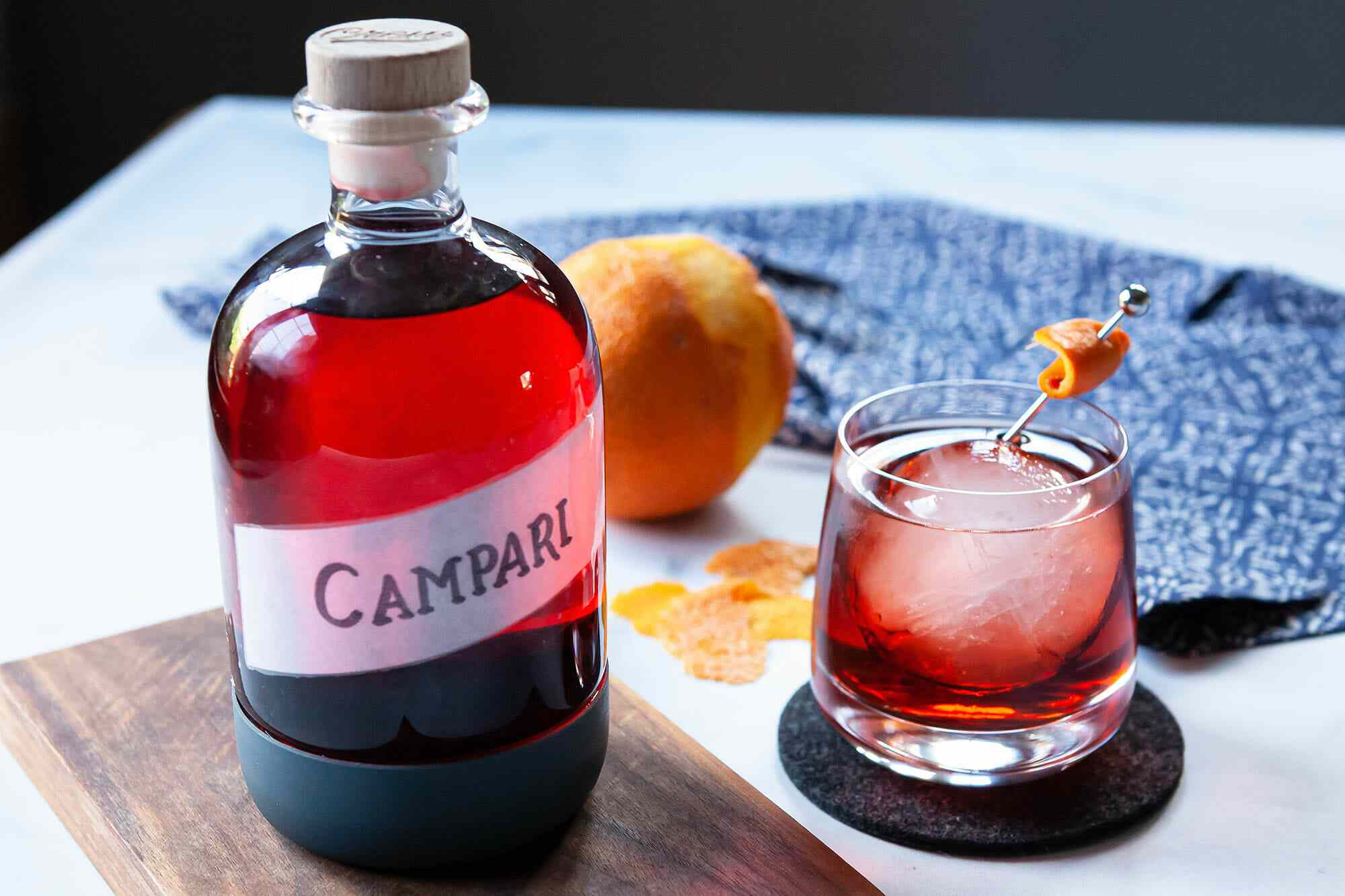 Glass jar filled with Campari substitute. A whiskey glass with a cocktail inside is to the right.