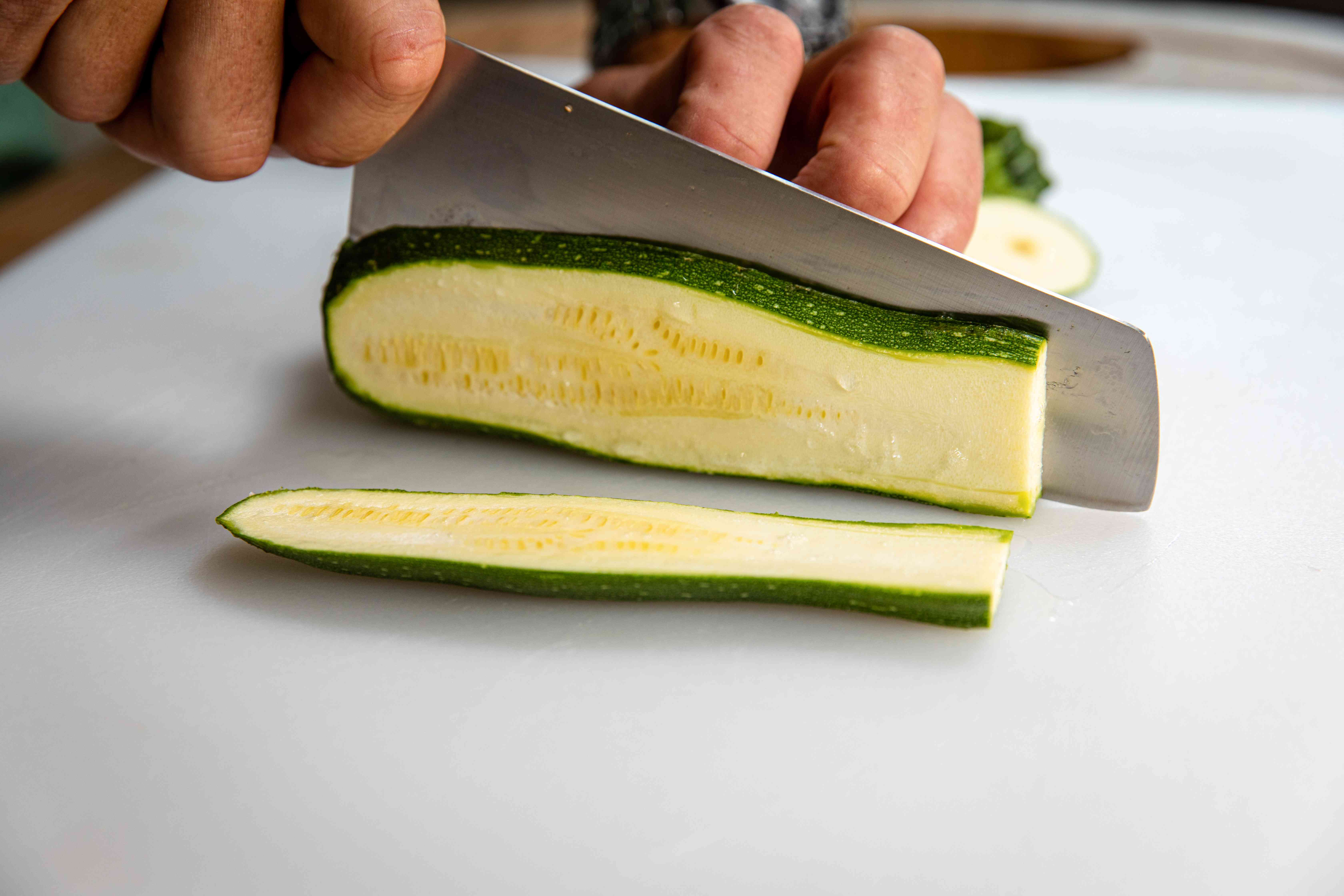 Thinly slicing zucchini to make easy grilled vegetable nachos.